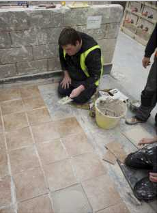 Student tiling the floor