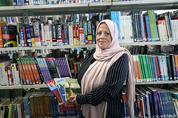 teacher holding books in the library