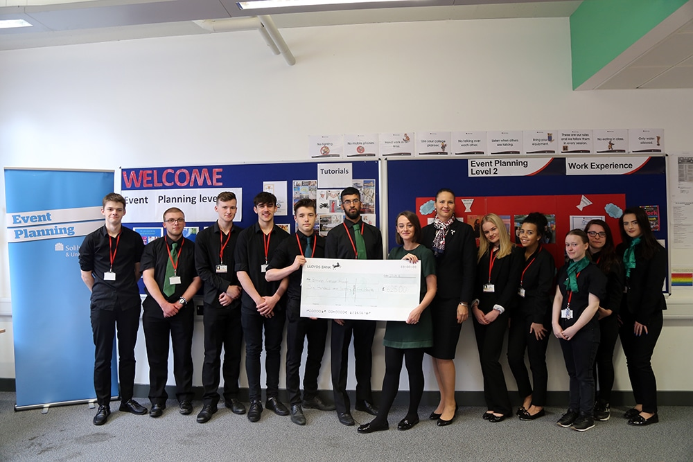 big cosy tea party cheque being held by the students
