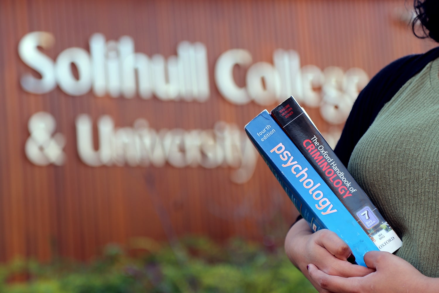 Girl stands holding books in front of college.