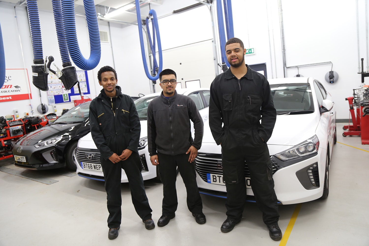 Motor Vehicle students in front of new hybrid vehicles