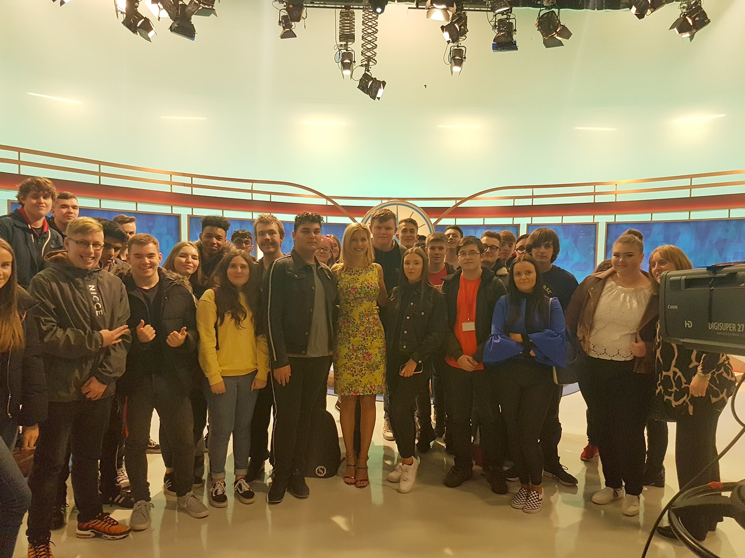 students standing with Rachel Riley