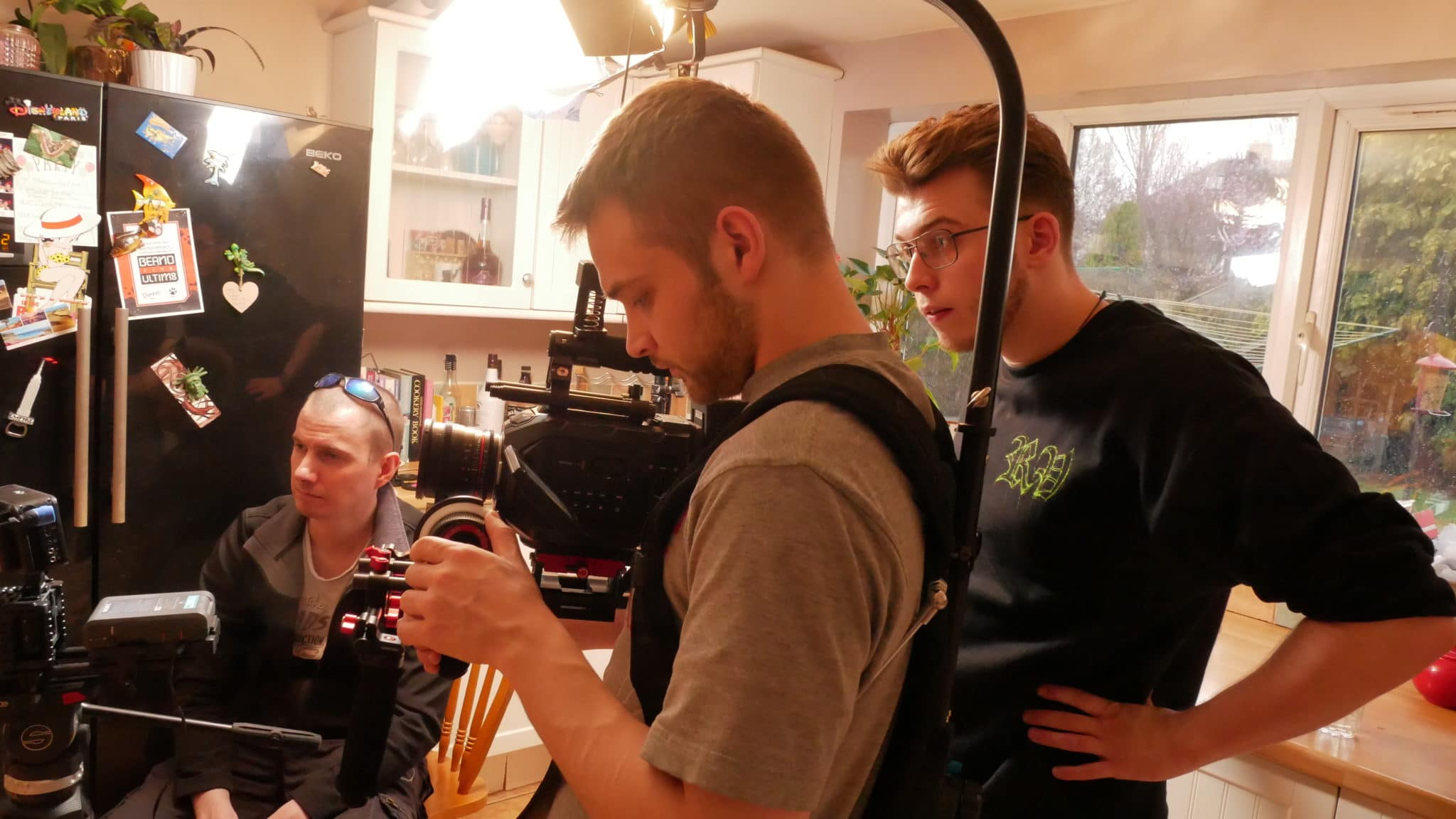 Daniel in the kitchen with a camera man filming