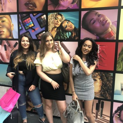 Hair & Media Make-Up students in front of makeup graphic wall