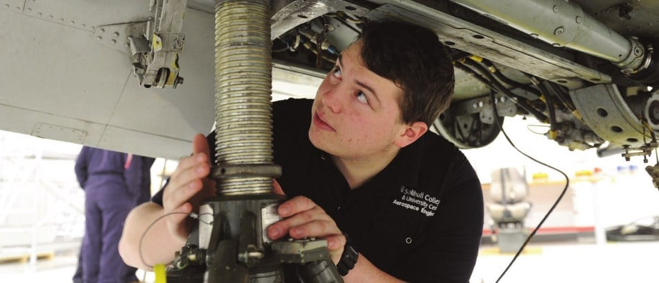 Aerospace engineering student inspects the undercarriage of a plane.