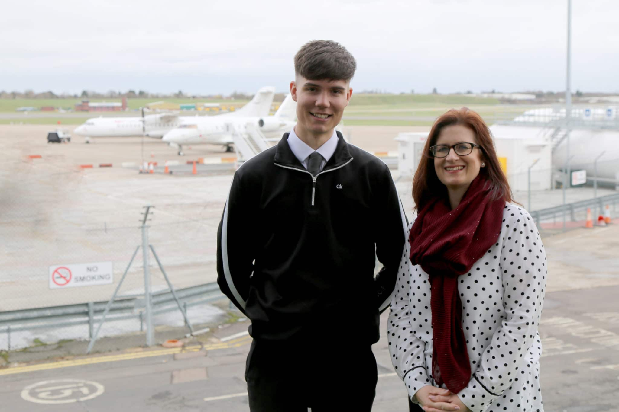 Joe stands with Jane in front of aircrafts at airport