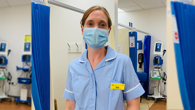 Liz stands in her nursing uniform on a ward.